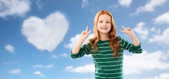 Le den röda haired flickan som visar fred över himmel arkivbilder