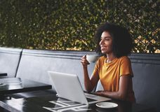 Le den säkra unga kvinnan som sitter i kafé med bärbara datorn på tabellen royaltyfri fotografi