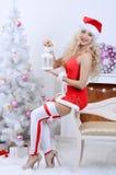 Le den santa kvinnan nära julgranen royaltyfri foto