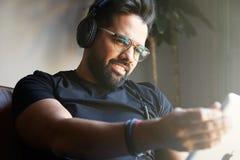 Le den skäggiga mannen i hörlurar som hemma lyssnar till musik på den elektroniska minnestavlan Koppla av och vilotidbegrepp Royaltyfri Fotografi