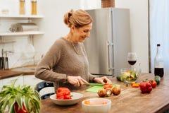 Le den snygga kvinnan som är i stort lynne, medan laga mat royaltyfri bild