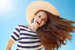 Le den stilfulla kvinnan med att fladdra hår mot blå himmel royaltyfria foton