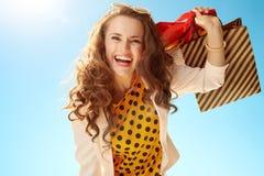 Le den stilfulla kvinnan med shoppingp?sar mot bl? himmel royaltyfria bilder
