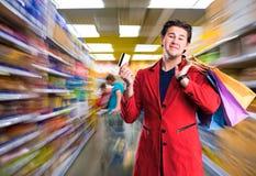Le den stiliga mannen med den shoppingpåsar och kreditkorten Royaltyfria Bilder