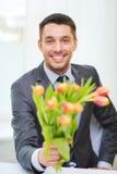 Le den stiliga mannen som ger buketten av blommor royaltyfri foto