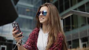 Le den tillfredsställda kvinnan i modeexponeringsglas och tillfällig kläder som sitter på momenten och den lyssnande musiken på h lager videofilmer
