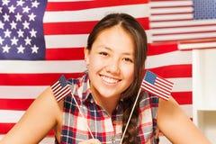 Le den tonårs- asiatiska flickan med flaggor av USA Arkivbilder