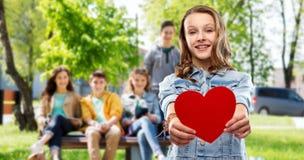 Le den tonårs- flickan med röd hjärta utomhus arkivbilder