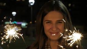 Le den tonårs- flickan på gatan på natten med tomtebloss Den unga kvinnan som firar en händelse det nya året, är kommande lager videofilmer