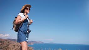 Le den touristic kvinnan som tycker om trekking beundra härligt naturhavs- och himmellandskap arkivfilmer