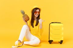 Le den turist- kvinnan för handelsresande i sommarkläder, frukt för ananas för hatthåll som ny mogen isoleras på den gula apelsin royaltyfria bilder