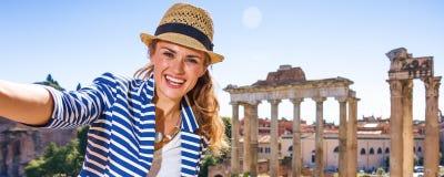 Le den turist- kvinnan framme av Roman Forum som tar selfie royaltyfri bild