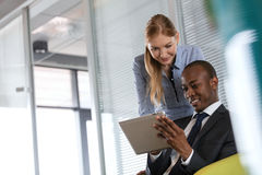 Le den unga affärskvinnan med den manliga kollegan som i regeringsställning använder den digitala minnestavlan royaltyfria bilder