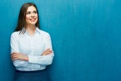Le den unga affärskvinnan mot den blåa väggen arkivbild