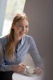 Le den unga affärskvinnan som har kaffe på tabellen i regeringsställning Arkivfoto