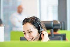 Le den unga affärskvinnan som i regeringsställning använder hörlurar med mikrofon Arkivbild