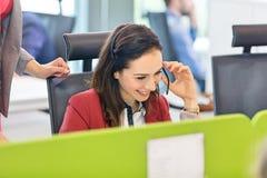 Le den unga affärskvinnan som i regeringsställning använder hörlurar med mikrofon Royaltyfri Foto