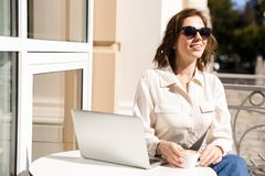 Le den unga affärskvinnan som sitter på kafét royaltyfri bild