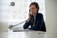Le den unga affärskvinnan som talar på svart landline, ringa royaltyfri bild