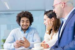 Le den unga affärsmannen genom att använda mobiltelefonen med kollegor i regeringsställning Arkivfoton