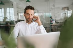 Le den unga affärsmannen som talar på en mobiltelefon på arbete royaltyfri fotografi