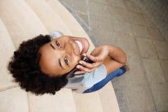 Le den unga afrikanska kvinnan som ser upp och använda mobiltelefonen Arkivbild