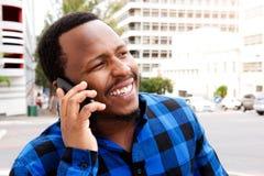 Le den unga afrikanska mannen som talar på mobiltelefonen i staden Royaltyfria Bilder