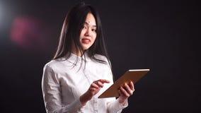 Le den unga asiatiska kvinnan som använder minnestavlaPCdatoren som isoleras på den svarta bakgrunden stock video