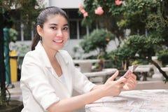 Le den unga asiatiska kvinnan som använder den smarta telefonen för mobil Internet av sakerbegreppet arkivfoton