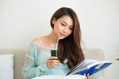 Le den unga asiatiska kvinnan som dricker grön nolla för fruktsaft för ny grönsak Arkivbilder