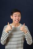 Le den unga asiatiska mannen som ger tummarna, up tecken Royaltyfri Fotografi