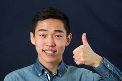 Le den unga asiatiska mannen som ger tummarna, up tecknet Arkivbild