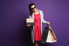 Le den unga brunettdamen, i röd klänning och solglasögon, med shoppingpåsar i hennes händer royaltyfri foto