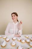 Le den unga damen som poserar, medan sitta nära muffin på tabellen Arkivbild