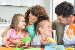 Le den unga familjen som gör konsthantverk på tabellen Royaltyfria Foton