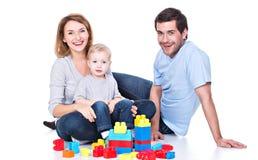 Le den unga familjen som spelar med en behandla som ett barn Fotografering för Bildbyråer