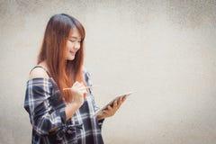 Le den unga härliga asiatiska kvinnan som tänker med handstil, boka på betongväggbakgrund bilder för tappningeffektstil Fotografering för Bildbyråer