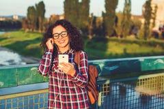 Le den unga kvinnan eller den tonårs- flickan med smartphonen och headphon Arkivbilder