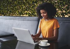 Le den unga kvinnan i kafé som skriver på bärbara datorn royaltyfri fotografi