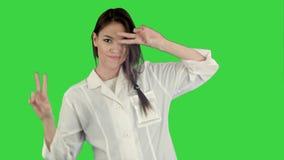Le den unga kvinnan i labblaget som gör rolig dans på en grön skärm, Chromatangent stock video