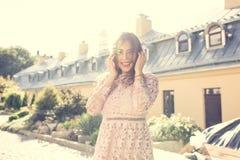Le den unga kvinnan i den trendiga klänningen som in poserar på gatan Arkivbild