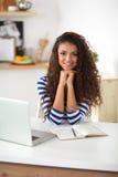 Le den unga kvinnan med bärbara datorn i köket på Arkivbild