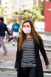 Le den unga kvinnan med den skyddande maskeringen som går runt om gatan i staden med luftförorening, stadsbakgrund Arkivbilder