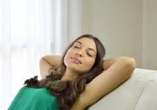 Le den unga kvinnan med grön ärmlös tröja som kopplar av på ett hemmastatt sammanträde för soffa på en soffa i vardagsrummet royaltyfri bild
