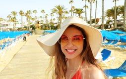 Le den unga kvinnan med sugrörhatten och solglasögon på stranden som ser kameran arkivbild