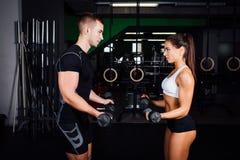 Le den unga kvinnan och den personliga instruktören öva i idrottshall Arkivfoton