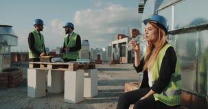 Le den unga kvinnan på konstruktionsplats, dricksvatten och att bära en säkerhetshjälm och en hög synlighetsväst lager videofilmer