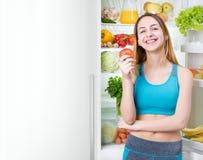 Le den unga kvinnan som äter ett äpple och mycket blir nära kylen av hälsokost Royaltyfria Foton
