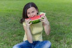 Le den unga kvinnan som äter vattenmelon Royaltyfri Foto