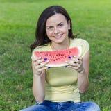 Le den unga kvinnan som äter vattenmelon Royaltyfria Bilder